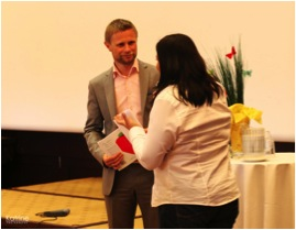 The Minister of Health and Care Services receives a copy of 'Touching rainbows' at the first conference in Kristiansand on children's palliative care in April 2012