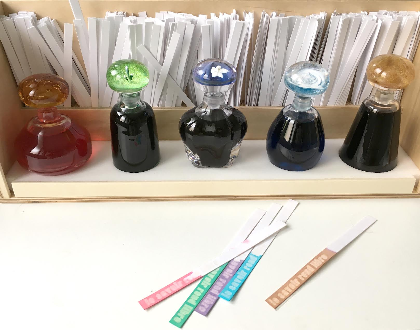 Materials consist of three presentation boxes of five coloured perfumes in  five vials and strips of scent paper concealing phrases.